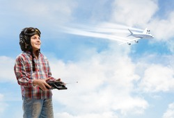 little boy in a helmet pilot keeps remote control, in the background plane and sky