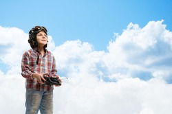 little boy in a helmet pilot keeps remote control, in the background sky and clouds