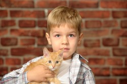 Little boy in a plaid shirt with a red kitten in his hands against a brick wall background