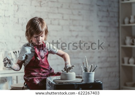 little boy in a pottery