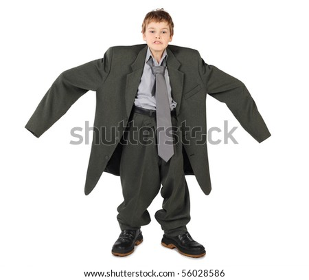 little boy in big grey man's suit and boots hands at sides isolated on white background
