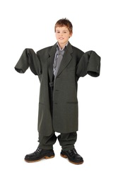 little boy in big grey man's suit and boots standing isolated on white background