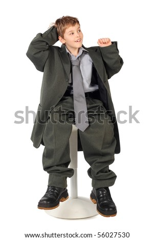 little boy in big grey man's suit sitting on chair isolated on white background - stock photo