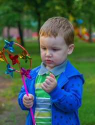 Little boy in blue clothes plays with children's paper colorful windmill in the park