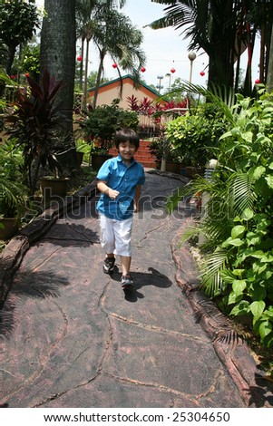 Little boy in blue shirt running in the garden on a sunny day