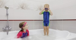 Little boy in blue swimming glasses is jumping in the water in a bath. A girl in swimsuit catching and helping her brother.