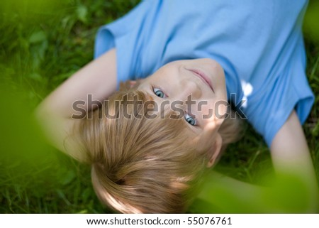 little boy in blue t-shirt lying on the grass  under tress - stock photo