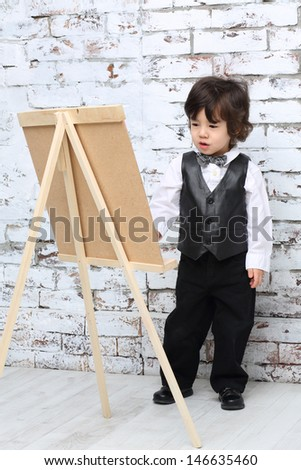Little boy in bow tie stands next to easel in studio with white brick wall.