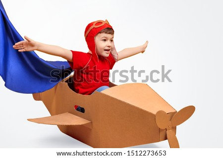 Little boy in bright costume stretching out arms and sitting in carton aircraft while imagining to be pilot against white background #1512273653