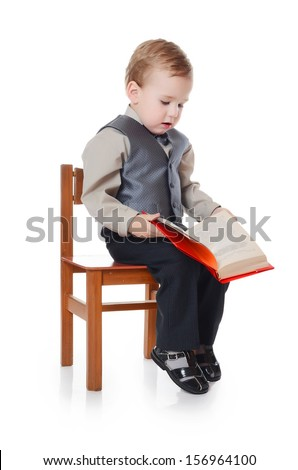 Little boy in business suit reads book