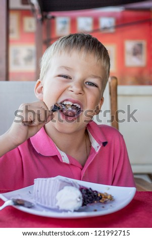 little boy in cafe eats a dessert