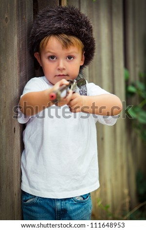 Little boy in coon skin cap pointing his toy rifle