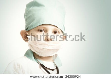 Little boy in doctor cap with mask closing mouth