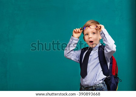 little Boy in eyeglasses with big backpack. School, kid, rucksack. Cheerful smiling little boy opens his mouth in surprise. Looking at camera. School concept. Back to School