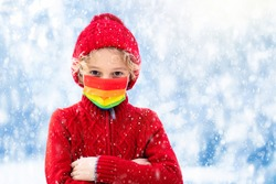 Little boy in face mask playing in snow winter park. Kids wear protective mask. Safe holiday celebration. Outdoor fun during coronavirus outbreak. New normal and social distancing in covid-19 pandemic