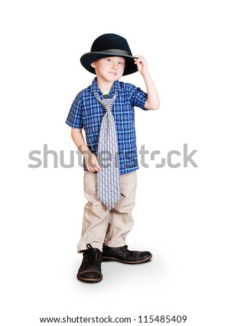 Little boy in father's shoes; tie and hat