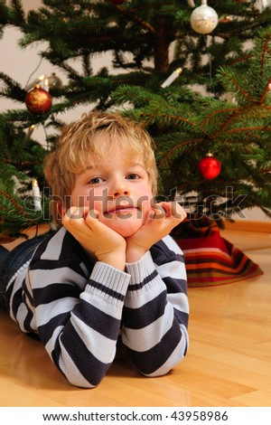 little boy in front of christmas tree - stock photo