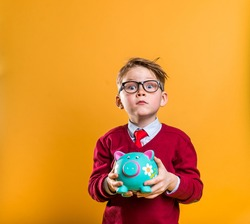 Little boy in glasses and tie with piggy bank in hands. School kid counts money, isolated on yellow background. How to earn money. Business education at school.