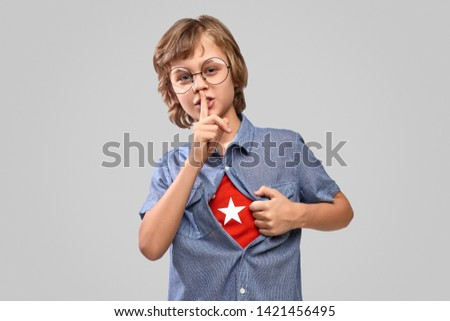 Little boy in glasses showing superhero emblem under shirt and keeping finger near lips while revealing identity and asking to keep secret against gray background