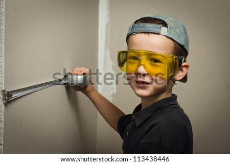 Little boy in goggles with a tape measure