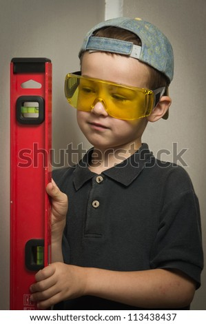 Little boy in goggles with a wall level