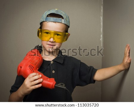 Little boy in goggles with electric drill