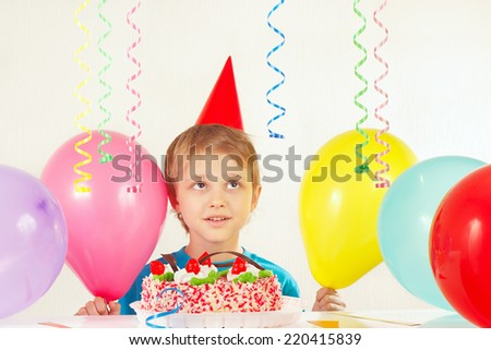 Little boy in holiday hat with a festive cake and balloons