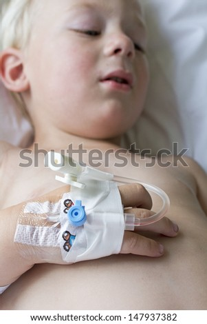 Little boy in hospital with tubes in hands