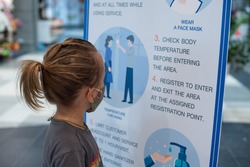 Little boy in mask reading the rules about Covid-19 coronavirus and clean his hands with sanitizer before entering shopping mall