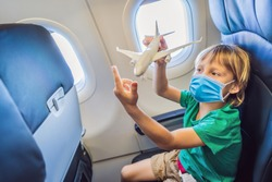 Little boy in medical mask play with toy plane in the commercial jet airplane flying on vacation Tourists fear the 2019-ncov virus. Medical masked tourists