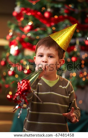 Little boy in new year\'s eve hat blowing horn, looking at camera.