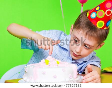 Little boy in party hat tasting birthday cake