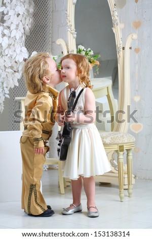 Little boy in pop retro suit kisses a girl in white dress