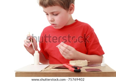 little boy in red T-shirt crafts at small table, boxcutter, glue