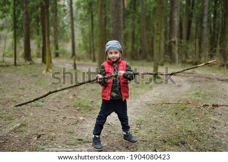 Little boy in red vest is playing with big branch and having fun in forest on early spring day. Activity for children. Outdoor recreation for family with kids ストックフォト ©