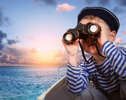 Little boy in sailor's uniform with binocular in the boat