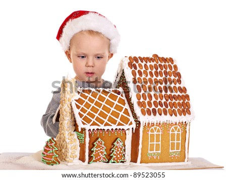 Little boy in santa hat with gingerbread house on white background