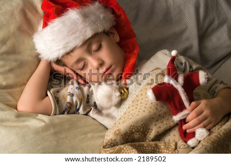 Little boy in Santa's hat sleeping with a toy in a hand