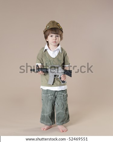 stock photo : Little boy in soldier's uniform with a gun. Studio shot