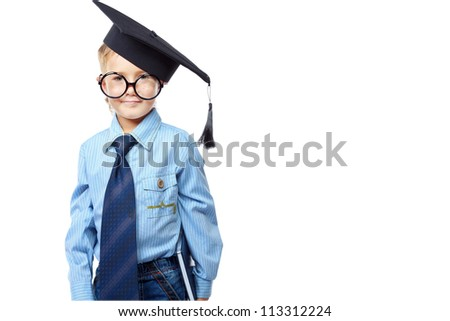 Little boy in spectacles and academic hat standing over white background. Isolated.