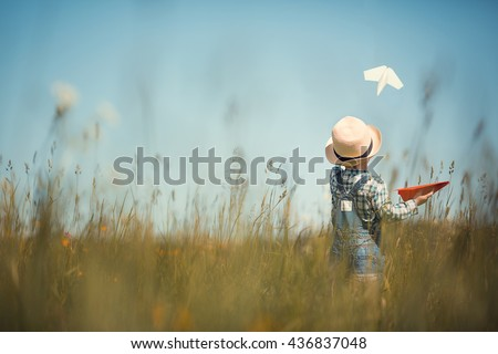 Photo of Little boy in straw hat is launching paper planes. One plane is white and the second is red. Back view. Image with selective focus and toning.