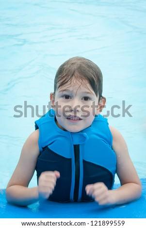 Little boy in swimming pool wearing blue life vest