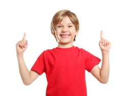 Little boy in t-shirt pointing at something on white background