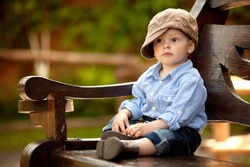 little boy in the blue shirt and brown cap is sitting on the wooden bench in the park