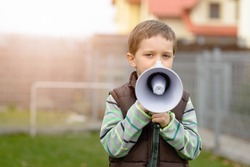 Little boy in the brown vest shouts something into the megaphone in the garden