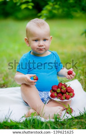 little boy in the garden with strawberries