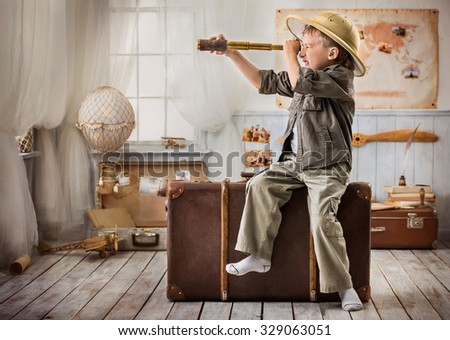 Little boy in the image of a tourist looking through a telescope sitting on a big suitcase