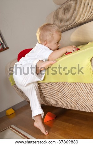 Little boy in white is climbing on sofa