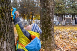 Little boy in yellow jacket, striped hat, with backpack plays with blue toy car on trunk of old tree in city Park in autumn. Concept of child development. Games and entertainment with baby.