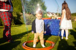 Little boy inside the soap bubble. Bubbles show, entertainment for kid's birthday party, summer day, outdoors